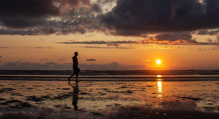Ragazzo che cammina sulla spiaggia al tramonto